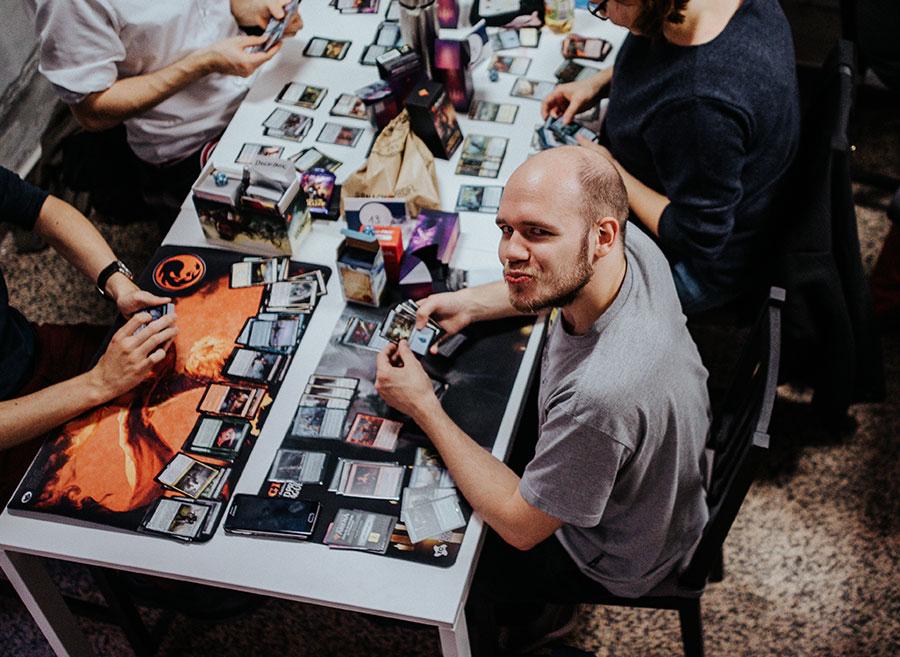 Ein Magic-Spieler beim Deckbau, der eine Schnute für die Carmera macht.